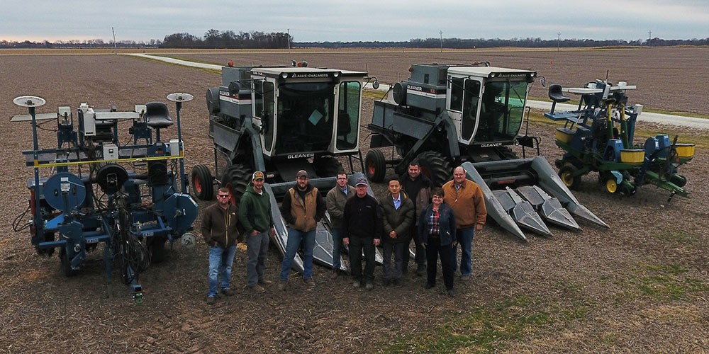 A group of people standing in front of farm equipment