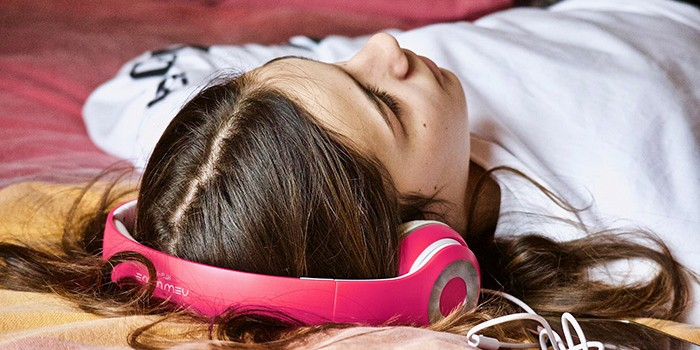Girl laying on a bed with headphones on
