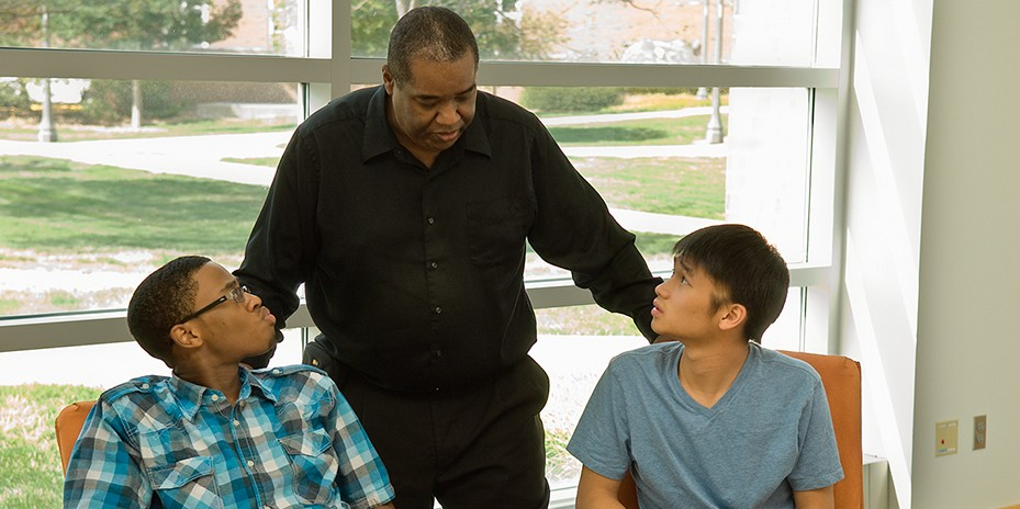 photo of Jesse Thompson with two sutdents in the Heritage Room of LIAC.