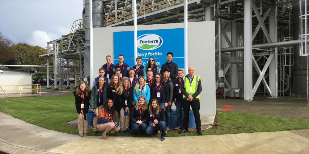 "Group in front of a sign that says ""Fonterra, dairy for life"""