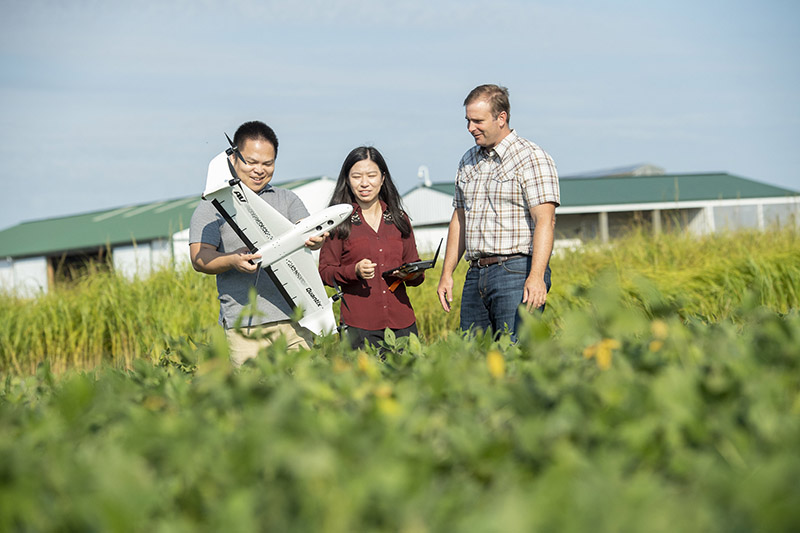 Faculty and students discuss a type of drone used for agricultural applications
