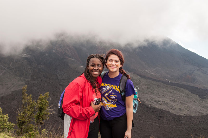 Two students posing in front of mountain and fog