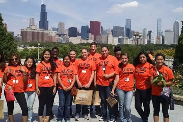Group of hight school students wearing orange Illinois t-shirts in front of the Chicago skyline.