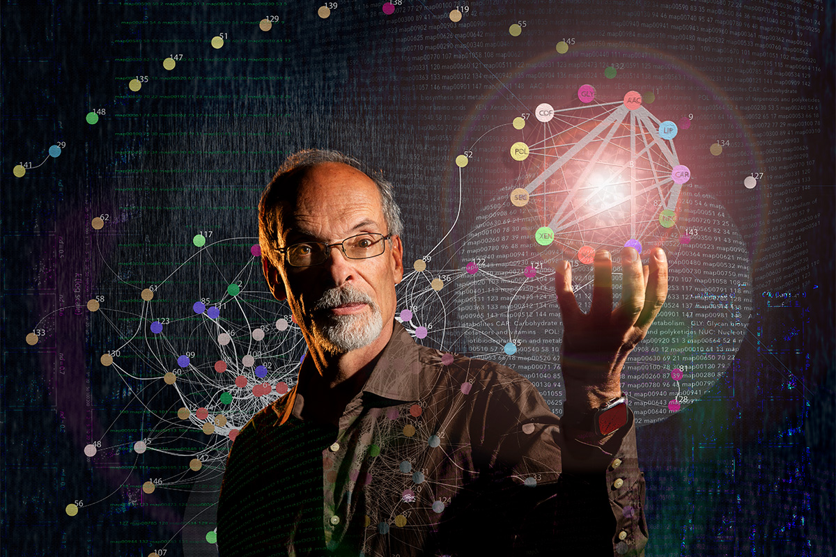 Gustavo Caetano-Anolles surrounded by depiction of molecular networks. Image by Fred Zwicky.
