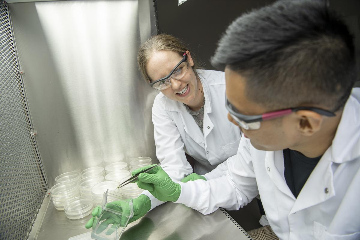 Sarah Hind, left, works with student in laboratory