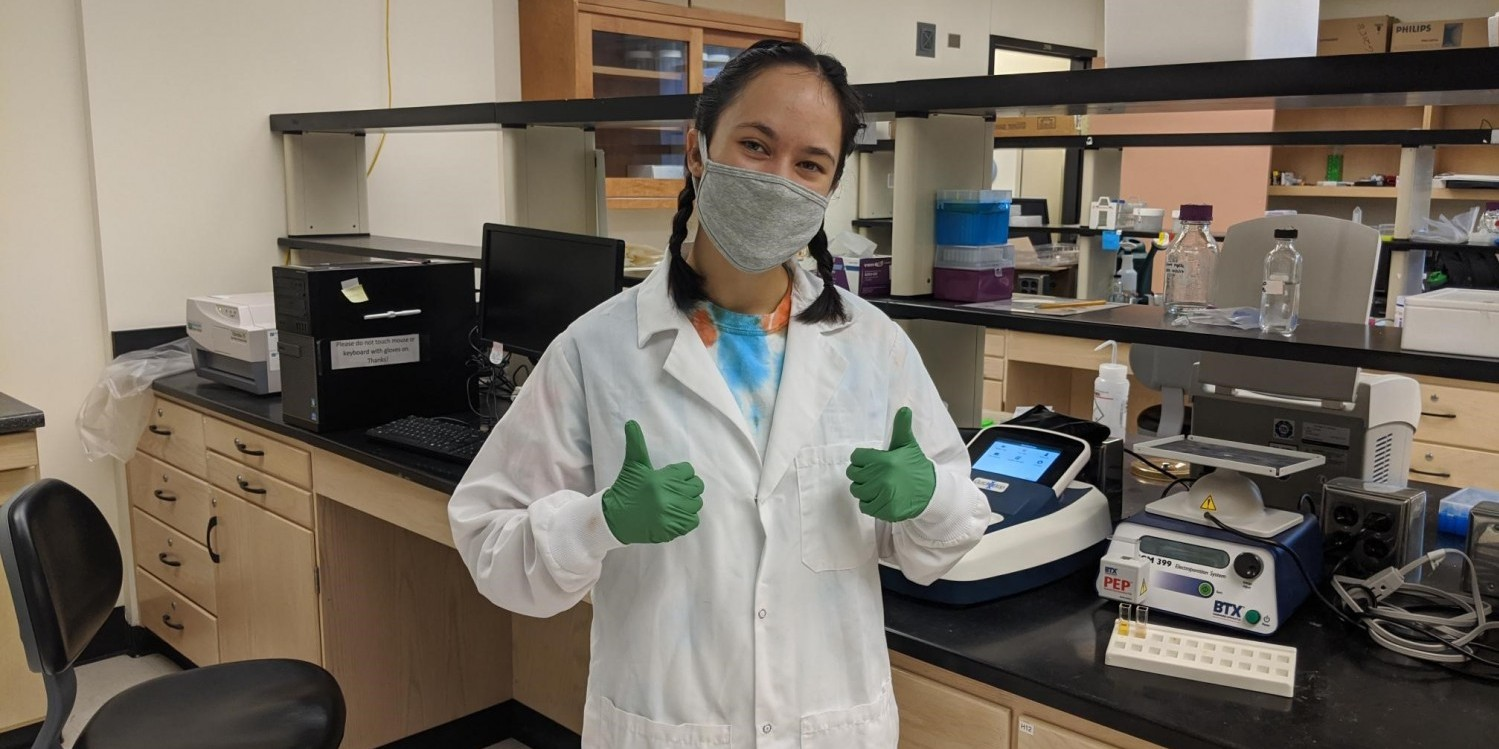 student in laboratory giving thumbs up