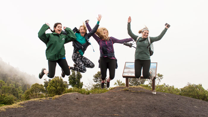 Group of students jumping on top of mountain.