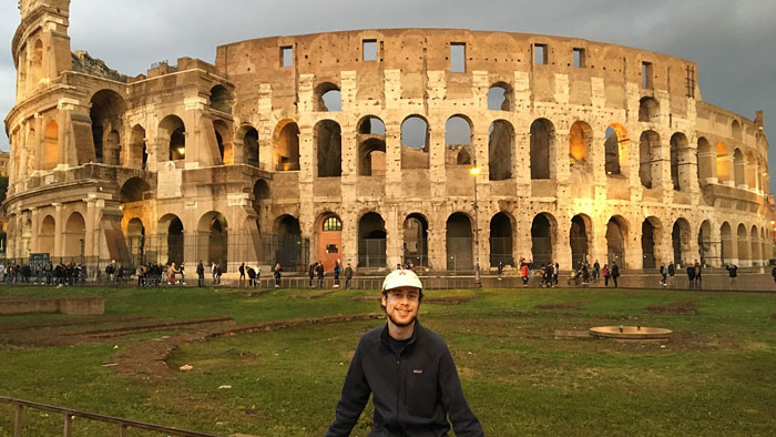 Male student posing in front of the Colosseum in Rome.