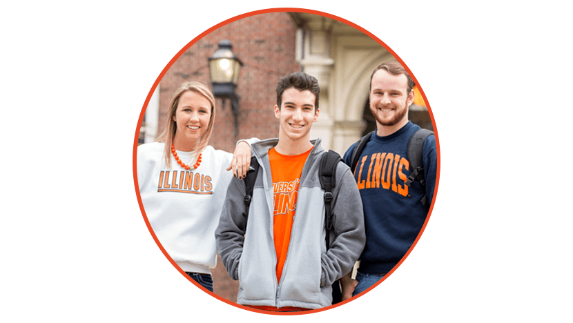 Photo of three students standing together by a building